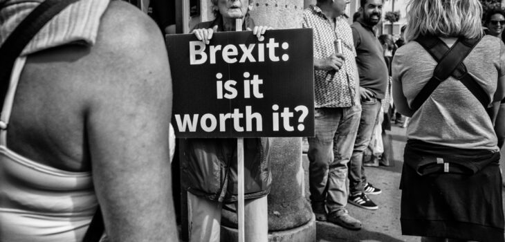 A woman holds up a sign saying Brexit is it worth it, on the streets of Bristol.